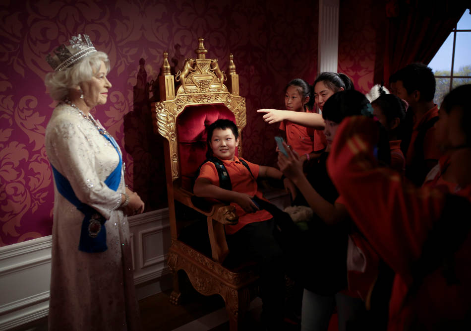 A student, center, sitting on a mock-up of the royalty chair, looks at a wax figure of Britain's Queen Elizabeth II, while others take souvenir photos, at the Madame Tussauds Museum in Beijing, China Friday, Sept. 19, 2014.  Scottish voters have resoundingly rejected independence, deciding to remain part of the United Kingdom after a historic referendum that shook the country to its core. (AP Photo/Andy Wong)