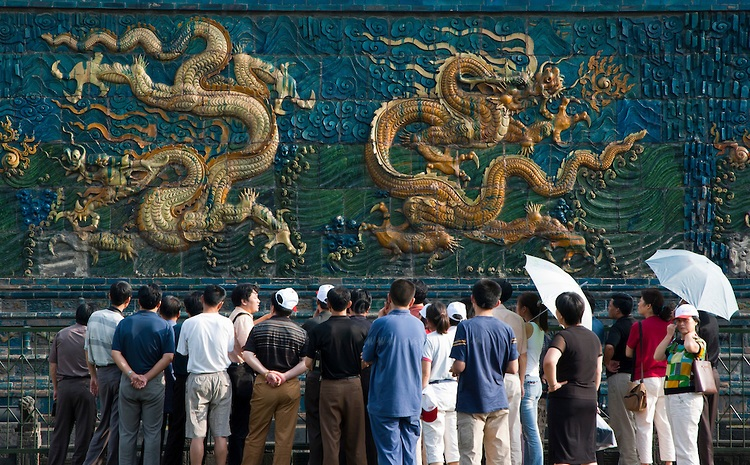 Tourists admiring the decorative artwork of dragons on the Nine Dragon Screen in Datong, Shanxi, China.